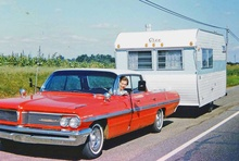 An early sixties Pontiac two tone red and white hardtop towing a Cree trailer on ...