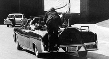 JFK's limousine speeds from the scene of the shooting but it's already too late.