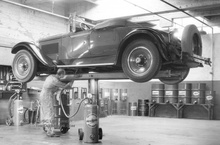 A circa 1928 Packard Roadster is seen above up on a hydraulic lift being greased, ...