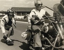 Kid on skateboard slipstreams grand dad's Harley.