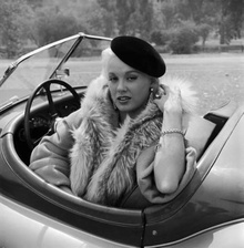 Blonde in Jaguar XK120 Roadster.